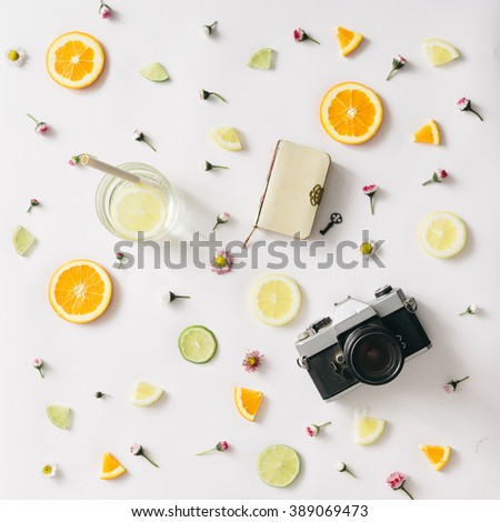 Colorful pattern made of orange, lemon, lime and flowers with lemonade and vintage camera and notebook.