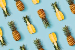 Colorful pattern of pineapples on pastel blue background. Top view. Minimal tropical fruit summer concept.