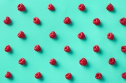 Colorful pattern of raspberries on blue background. From top view