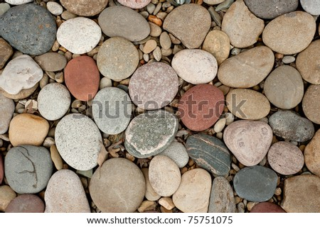 Colorful pebbles laying on the ground in a zen-like state. Stones are very smooth.