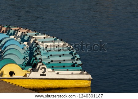Colorful pedal boats all lined up and floating on the lake. Wide color range boats. #1240301167