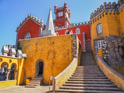 Colorful Pena Palace or Palácio da Pena stands on the top of a hill in the Sintra Mountains, in the blue sky background. Exterior of national monument with a variety of architectural styles and colors