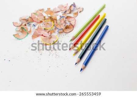 Colorful pencil crayons on white desktop with pencil shavings