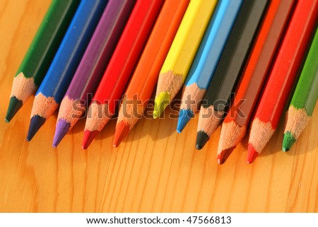 Colorful pencil crayons on wooden background