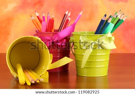 Colorful pencils and felt-tip pens in pails on color background