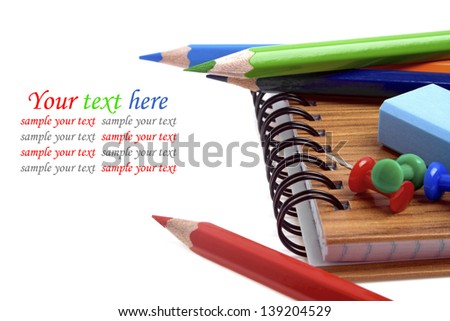 Colorful pencils and notebook isolated over white with copyspace