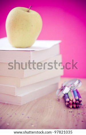 colorful pencils, apple and books for school