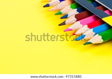 Colorful pencils in box on yellow background with place for text.