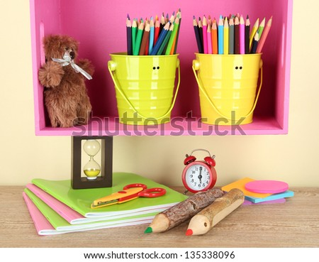 Colorful pencils in pails on shelf on beige background