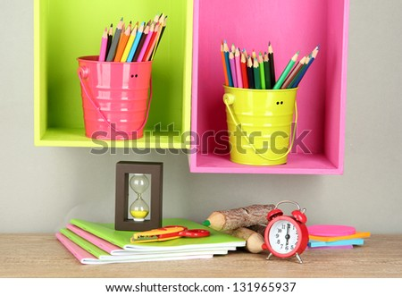 Colorful pencils in pails on shelves on beige background