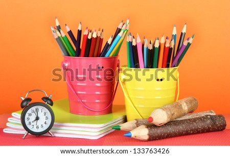 Colorful pencils in two pails with copybooks on table on orange background