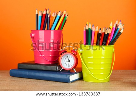 Colorful pencils in two pails with writing-pad on table on orange background