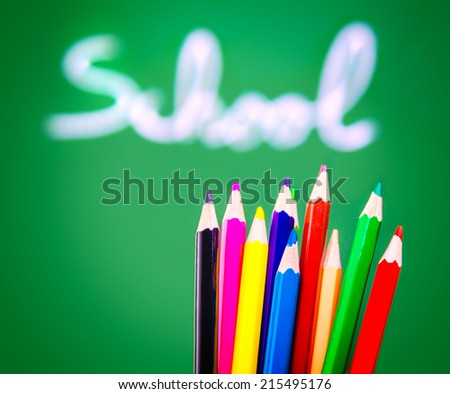Colorful pencils on green chalkboard background, soft focus of handwriting word, lesson of art, back to school concept