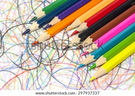 Colorful pencils on hand drawn scribble circles background