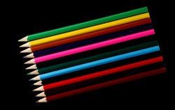 Colorful pencils set arrangement, row isolated on black background, top view