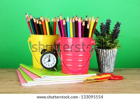 Colorful pencils with school supplies on table on green background