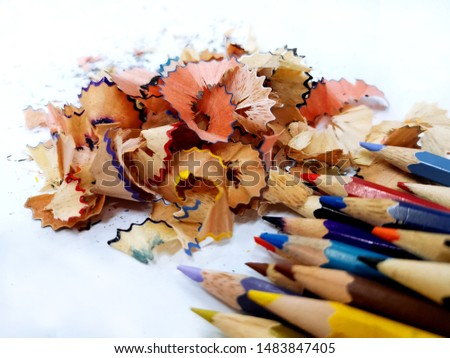Colorful pencils with sharpeners isolated white background. There are a lot of wood chips from the pencil beside the pencil.