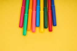 colorful pens on yellow background