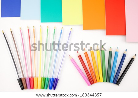 Colorful pens placed in a portrait orientation and notes on a white background