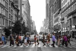 Colorful people walking across a busy intersection in a black and white Manhattan cityscape in New York City NYC