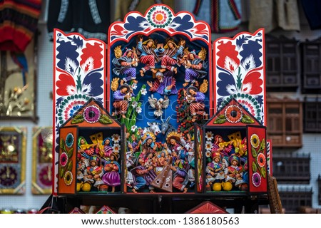 Colorful Peruvian artisanal Retablo for sale at street Indian market in Miraflores, Lima. A traditional devotional handcraft with iconography derived from traditional Catholic church art. #1386180563