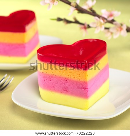 Colorful Peruvian heart-shaped jelly-pudding cakes called Torta Helada with a blooming peach branch in the back (Selective Focus, Focus on the front of the first cake) - stock photo