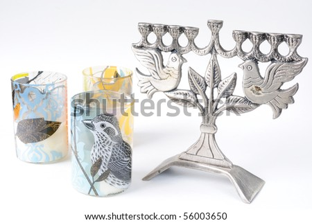 Colorful picture of a bird on a candle holder next to a menorah with peace doves.