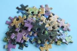 Colorful pieces of incomplete jigsaw puzzles on blue background, selective focus. Team business solutions, success and strategy concept.