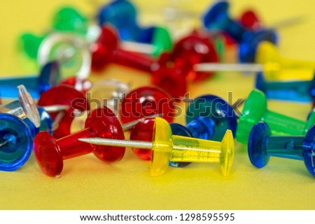 Colorful pile of drawing pins piled on a yellow background