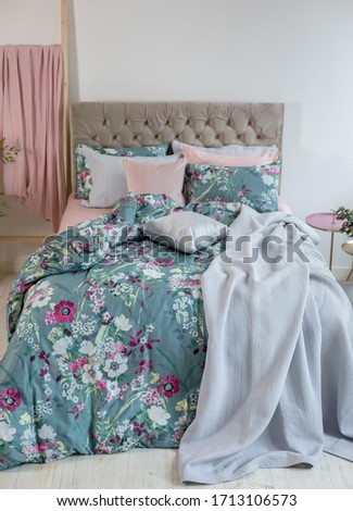 Colorful pillows, duvet and duvet case on a bed. Beautiful bed linen on a sofa. Bedroom with bed and bedding. Messy bed. Front view.
