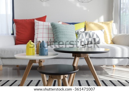 Colorful pillows on a sofa with little vase in foreground