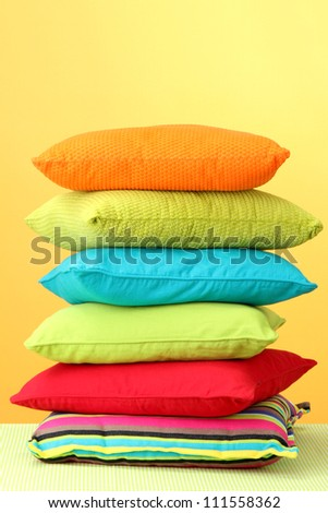 Colorful pillows on yellow background