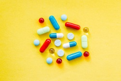 colorful pills and drugs in close up.assorted pills and capsules in medicine. drugs of various kinds and different colors. Medicine on yellow background