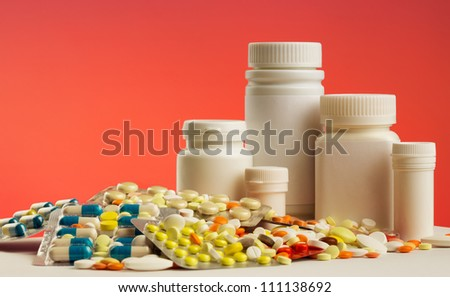 Colorful pills, capsules, dragee and white bottles
