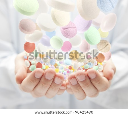 Colorful pills falling into open palms