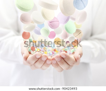 Colorful pills falling into open palms - stock photo