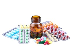 Colorful pills in blisters and bottle on white background