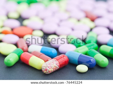 Colorful pills over dark background