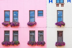 Colorful pink and white building with flowers in window boxes