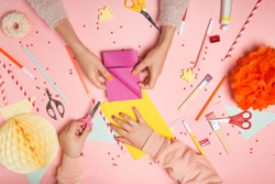 Colorful pink background with various party confetti, paper decoration, flags, stationary, DIY accessories with woman's and kid's hands making greeting card. Fat lay top view. Party arrangement