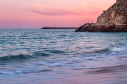 Colorful pink dreamy sunset over Atlantic Ocean coast on the beach of Albufeira city, Faro, Algarve, Portugal with soft long exposure water with limestone cliffs and lighthouse in the background