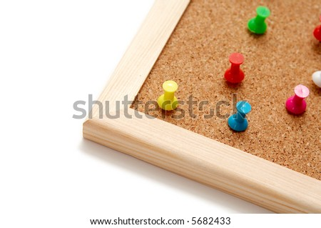 Colorful pins on a brown corkboard