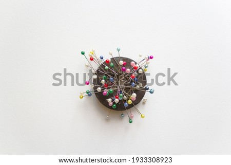 colorful pins on ring magnet isolated white background, magnetic pin cushion, tailor, sewing, fashion, design materials equipments, tools, diy, cloth fastening fabric, glass headed pin Photo stock ©