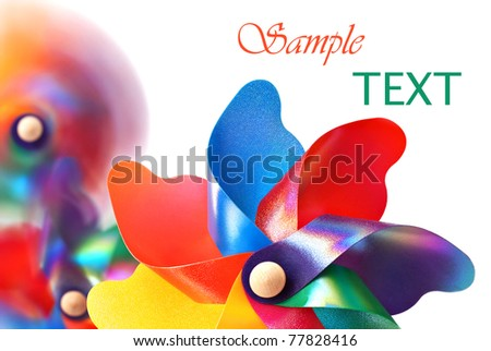 Colorful pinwheel with spinning pinwheels in soft focus in background.  Macro on white background with copy space.