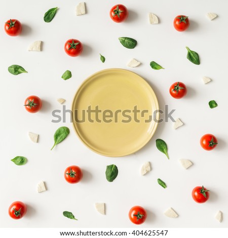 Colorful pizza ingredients pattern made of cherry tomatoes, basil and cheese on white background. Cooking concept.