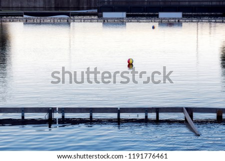 Colorful plastic ball floating over the calm water of a river and blank signboards behind. #1191776461