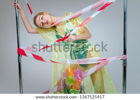 Colorful plastic cups. Skinny model wearing green body suit holding bag full of colorful plastic cups