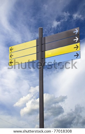 Colorful plastic informational signs with arrows. Show the direction. Against the blue sky with clouds