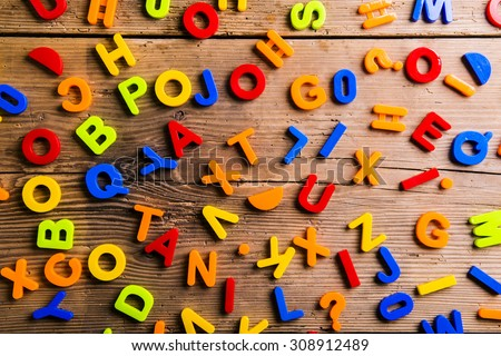 Colorful plastic letters and numbers laid on wooden background.