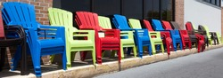 Colorful plastic resin Adirondack chairs in a row.